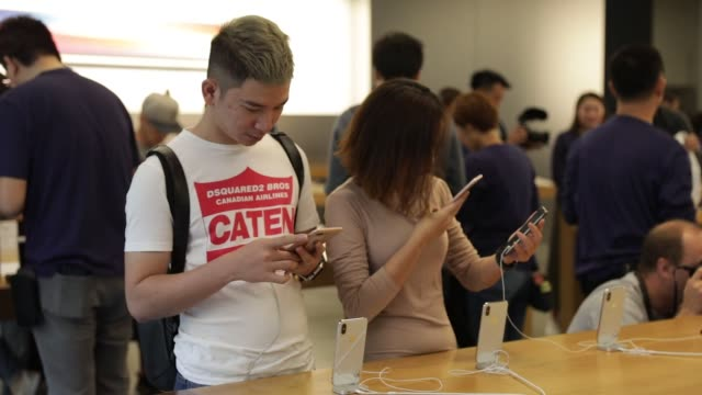 Employees assist customers purchasing the Apple Inc iPhone X at an Apple store during its launch in Hong Kong China on Friday Nov 3 Photographer...