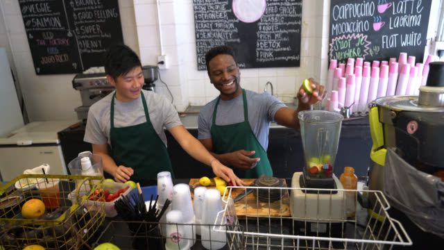 Employees at a juice bar working as a team one passing the fruits and the other cutting having fun