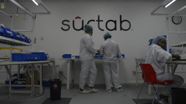 employees at the surtab manufacturing plant in port au prince haiti sit at a line of workstations assembling tablets with a surtab logo on the wall... - haarnetz stock-videos und b-roll-filmmaterial