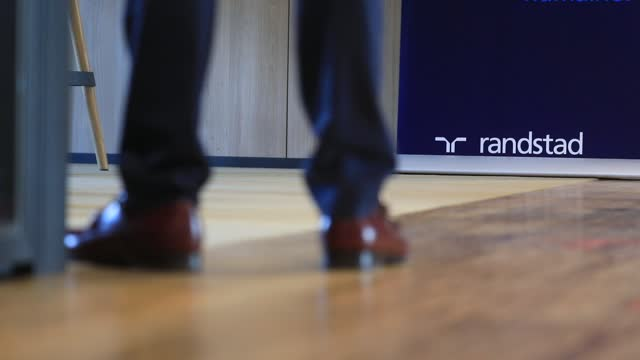 employees attend a meeting, the randstad company logo in the background on december 4 in saint-denis, france. dutch multinational human resource... - クラシファイド広告点の映像素材/bロール