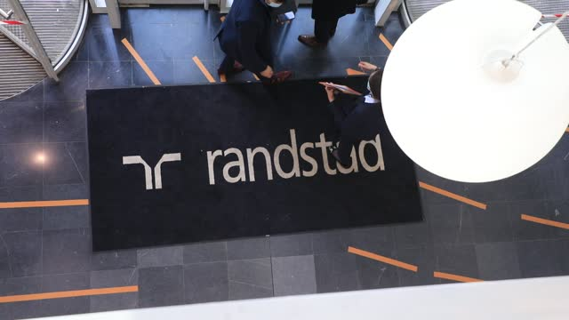 employees chat in the main hall of the french headquarters of the randstad company on december 4 in saint-denis, france. dutch multinational human... - クラシファイド広告点の映像素材/bロール