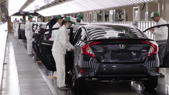 Employees check Honda Civic vehicles at the quality control station on the production line of the Honda Motor Co assembly plant in Prachinburi...