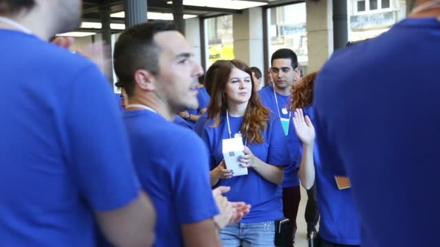 employees cheer and clap to warm up before welcoming customers at apple incs new spanish flagship store on puerta de sol square on its opening day in... - flagship store stock videos and b-roll footage