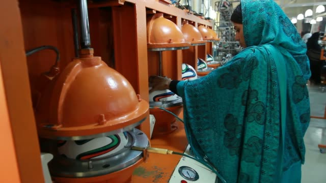 Employees clean Adidas AG Brazuca soccer balls on the production line at the Forward Sports Ltd factory An employee holds a hose inserted into the...
