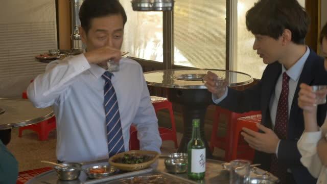 employees clinking soju (korean alcohol) glasses and drinking at a company get-together - skjorta och slips bildbanksvideor och videomaterial från bakom kulisserna