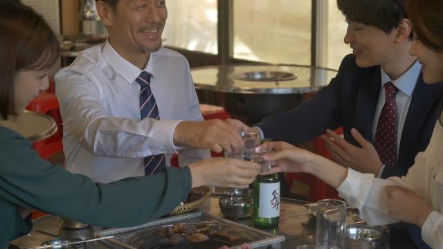 employees clinking soju (korean alcohol) glasses at a company get-together - skjorta och slips bildbanksvideor och videomaterial från bakom kulisserna