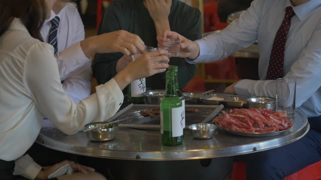 employees clinking soju (korean alcohol) glasses at a company get-together - korean ethnicity stock videos & royalty-free footage
