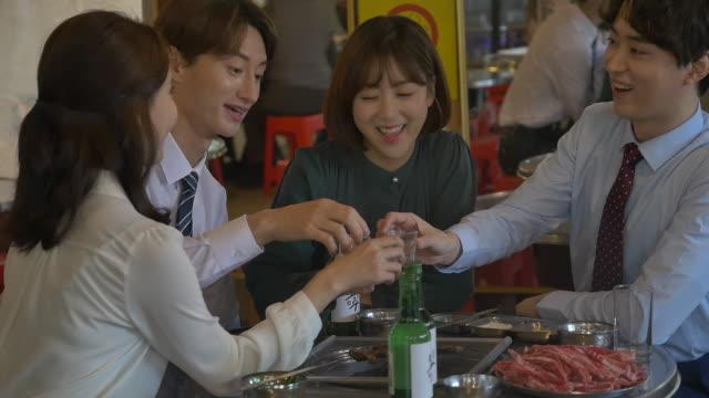 employees clinking soju (korean alcohol) glasses at a company get-together - 乾杯点の映像素材/bロール