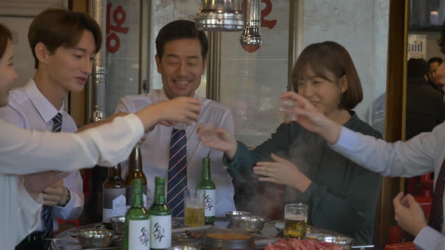 employees clinking soju (korean alcohol) glasses at a company get-together - hemd und krawatte stock-videos und b-roll-filmmaterial