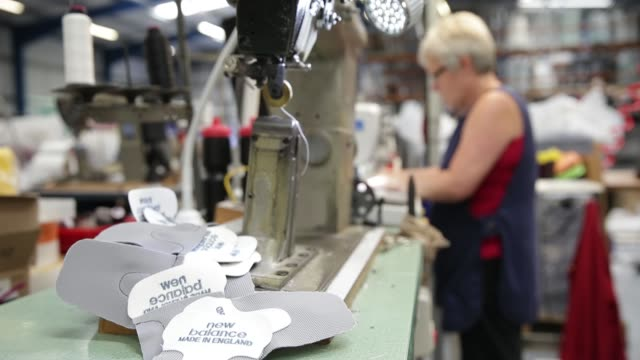 Employees cut patterns from sheet material for New Balance Athletic Shoe Inc trainers during the manufacturing process at the company's factory in...