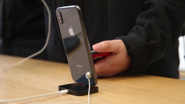Employees demonstrate iPhone X smartphones to customers at the Apple Inc store on Regent Street in London UK on Friday Nov 3 Photographer Luke...