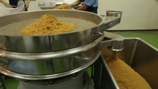 Employees empty a bag of garlic into a chopping machine at the Nithi Foods Co factory in the San Pa Tong district of Chiang Mai Thailand on Tuesday...