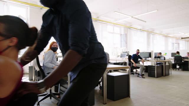 stockvideo's en b-roll-footage met medewerkers die plezier hebben op kantoor tijdens covid-19 - bureaustoel