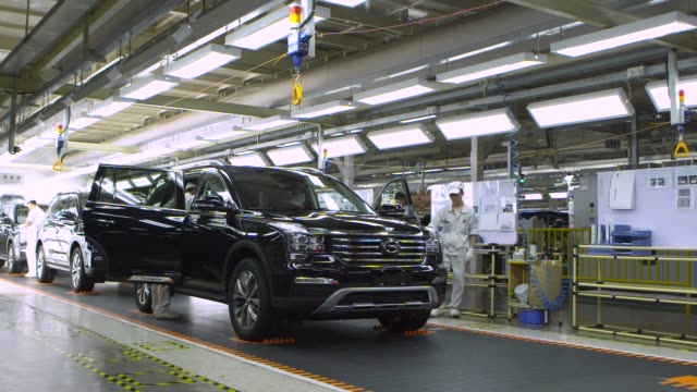 Employees inspect Trumpchi brand sport utility vehicles on a production line at the Guangzhou Automobile Group Co Ltd plant in Guangzhou China on...
