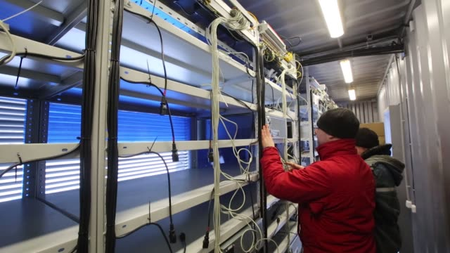 Employees install mining rigs inside a shipping container as a mobile cryptocurrency mining farm operated by BitCluster at Rodniki Industrial Park in...