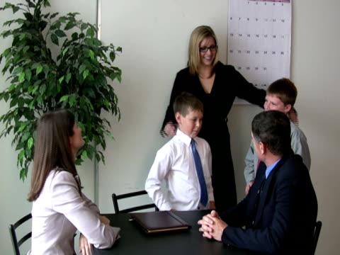 stockvideo's en b-roll-footage met employee's kids meet mother's bosses, co-workers - compleet pak