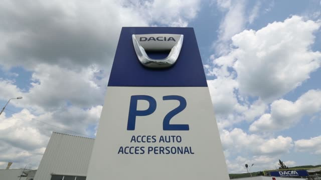 Employees leave after finishing their shift at the Renault Dacia factory in Pitesti Romania on Thursday July 3 A sign stands at the entrance to car...