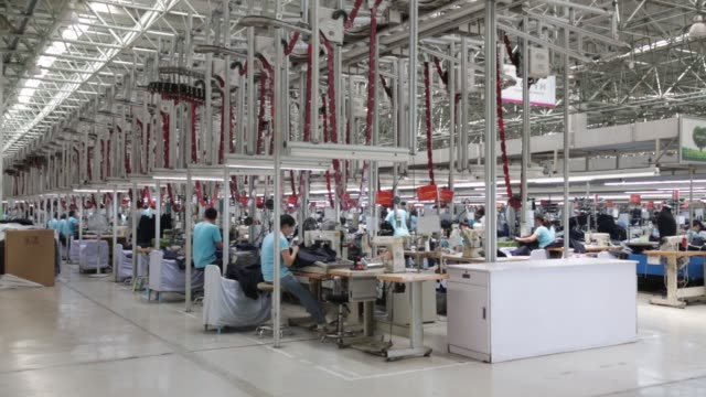 vídeos de stock e filmes b-roll de employees make suits at a factory operated by the shandong ruyi technology group in jining china on monday may 30 an employee sews a suit jacket at a... - casaco peça de roupa