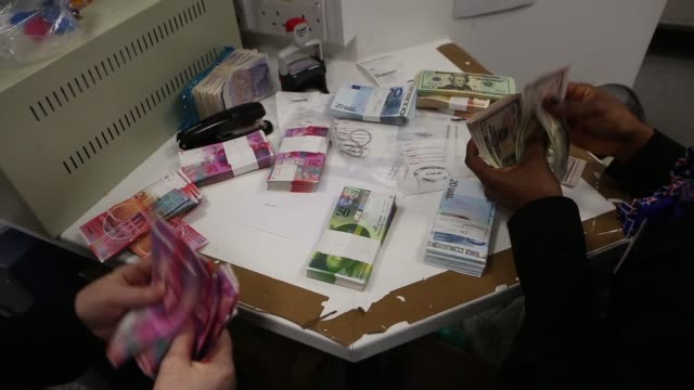 Employees manually count and sort euro notes at table inside aTravelex store operated by Travelex Holdings Ltd in London UK Employee places bundle of...