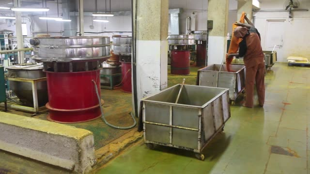 Employees monitor chilli powder being processed at a Suhana spice factory in Pune Maharashtra India on Monday Nov 28 A worker fills a container with...