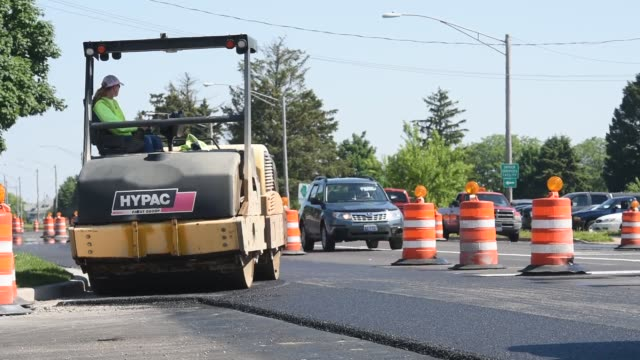 Employees of Advanced Asphalt Co pave a IL state highway in Streator Illinois US on Tuesday June 2 2015 Shots Road workers drive Hypac pavement...