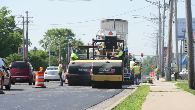 Employees of Advanced Asphalt Co pave a IL state highway in Streator Illinois US on Tuesday June 2 2015 Shots Wide shot of road work vehicles...