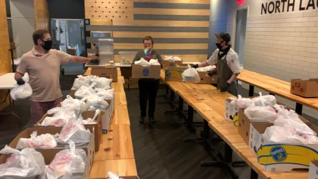 employees of bellwether restaurant carry boxes of prepared meals for distribution by feeding northeast florida on april 29 2020 in jacksonville... - meal stock videos & royalty-free footage