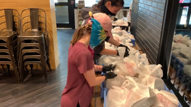 employees of bellwether restaurant place prepared meals in bags for delivery by feeding northeast florida on april 29 2020 in jacksonville florida... - meal stock videos & royalty-free footage