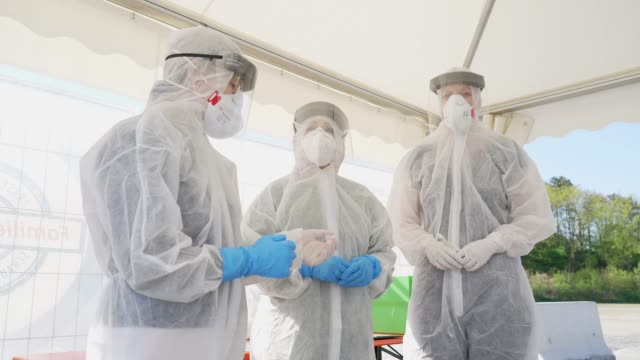 stockvideo's en b-roll-footage met employees of the berlin-mitte district health office adjust their ppe protective gear during a press opportunity at berlin's first drive-in covid-19... - berlin mitte