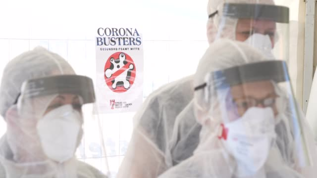 """stockvideo's en b-roll-footage met employees of the berlin-mitte district health office wear ppe protective gear, including masks, visors and suits, next to a sign that reads: """"corona... - berlin mitte"""