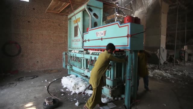 Employees operate cotton ginning machines at a Waqar Cotton Ginners factory in the district of Lodhran Punjab province Pakistan on Wednesday Oct 23...