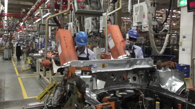 ws employees operate vehicle chassis welding machinery on the production line ms an employee operates vehicle chassis welding machinery - fahrgestell stock-videos und b-roll-filmmaterial