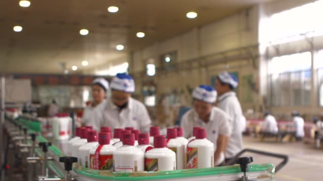 Employees package bottles of Moutai baijiu into boxes at the Kweichow Moutai Co factory in the town of Maotai in Renhuai Guizhou province China on...