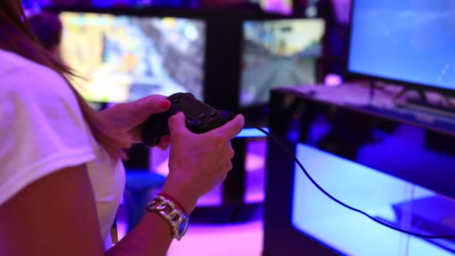 Employees play on Sony PlayStation 4 games consoles at the Sony Corp trade stand on the opening day of the IFA Consumer Electronics Show in Berlin...