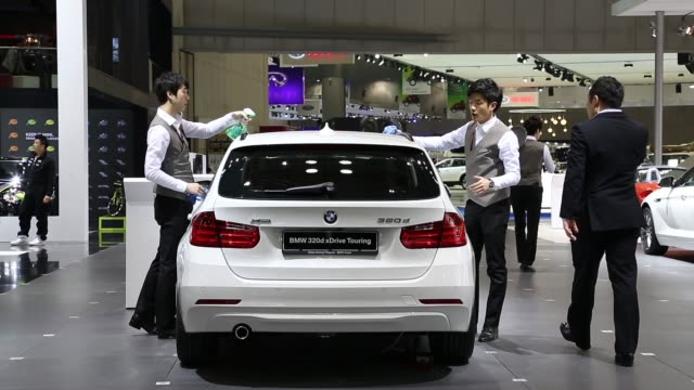 Employees polish a BMW 320d xDrive Touring car on display at the company stand at the 2013 Seoul Motor Show in Goyang Employees polish a BMW Gran...