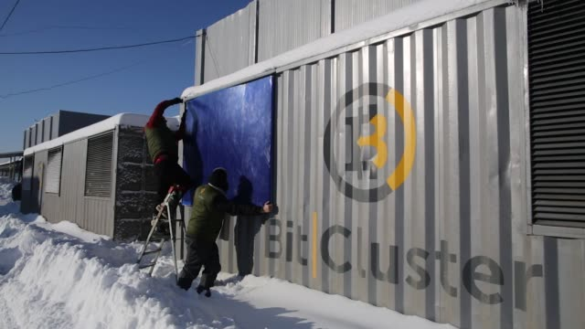 Employees prepare a shipping container as a mobile cryptocurrency mining farm operated by BitCluster at Rodniki Industrial Park in Rodniki Russia on...