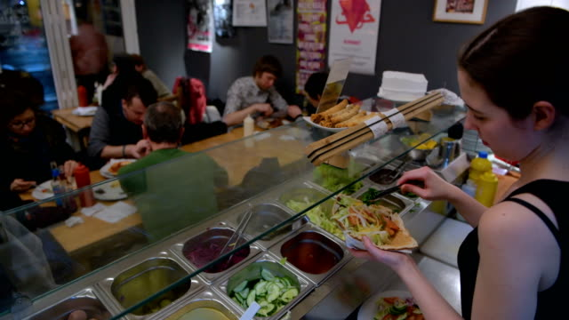 vídeos de stock, filmes e b-roll de employees prepare vegan dishes at vegan bistro voener on january 25 2018 in berlin germany voener offers classic fast food dishes such as burger... - vegan