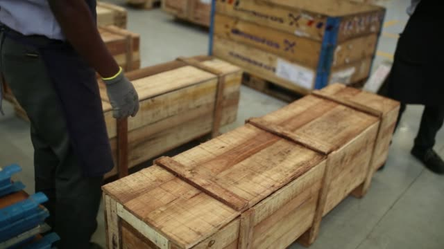 Employees prepare wooden boxes while packing water pumps at the Grundfos AS factory in Chennai India on Monday Nov 27 Employees walk through the...