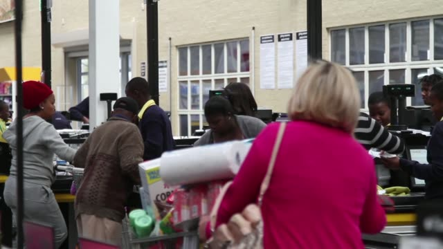 vídeos de stock, filmes e b-roll de employees process customers purchases at the check out desks of a makro cash and carry store operated by massmart holdings ltd in alberton south... - produto interno bruto