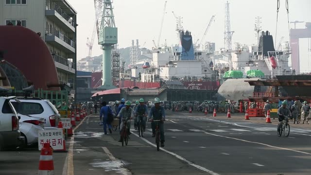 vidéos et rushes de employees ride motorcycles past traffic signs at the entrance of the hyundai mipo dockyard co shipyard an affiliate of hyundai heavy industries co in... - tôle