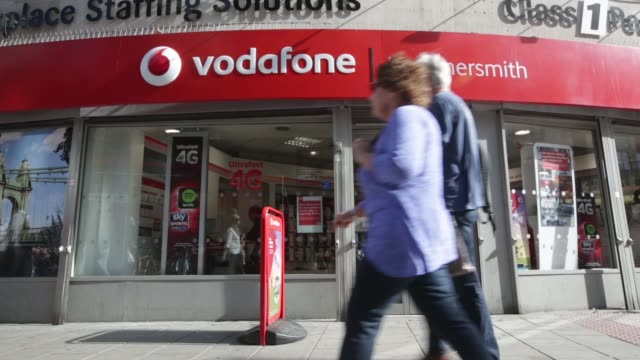 employees serve customers at a counter inside a vodafone store operated by vodafone group plc in london uk on monday sept 02 pedestrians pass a... - plc stock videos & royalty-free footage