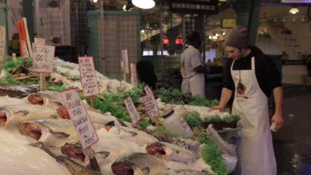 vídeos de stock, filmes e b-roll de employees shovel ice on fish market shelf - pike place market