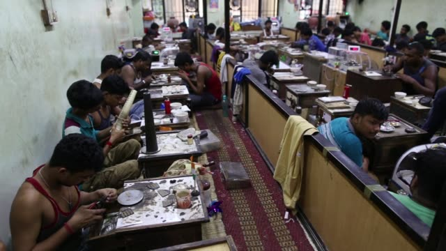 Employees sit working at a PN Gadgil Jewellers Pvt workshop in Pune India on Monday Aug 17 An employee inspects gold jewelry at a PN Gadgil Jewellers...