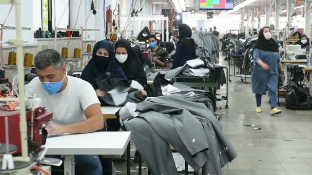 employees sitting in a row sewing clothes in tehran clothing factory. workers wearing protective face masks manufacture iranian brand clothing,... - tailored clothing stock videos & royalty-free footage