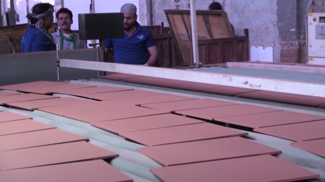 Employees stack tiles from a conveyor at the Shabbir Tiles Ceramics Ltd production facility in Karachi Pakistan on Wednesday Dec 6 Tiles move along a...