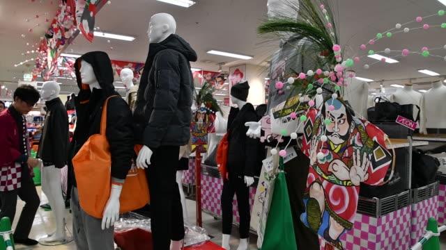 employees stacking merchandise at aeon style itabashi store, tokyo, japan, on thursday, december 26, 2019. - 百貨店点の映像素材/bロール