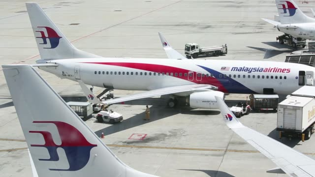 employees stand next to a malaysian airline system bhd boeing co 737 aircraft at kuala lumpur international airport in sepang malaysia on saturday... - malaysia stock videos & royalty-free footage