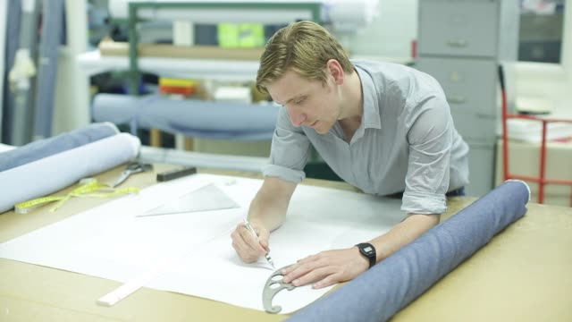 Employees trace new fabric designs and iron down garments at Drake's factory in Chard UK on Tuesday July 7 2015 Shots over the shoulder shot of man...