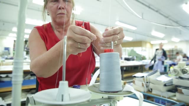 Employees use sewing machines to sew together shirts and fabrics at Drake's factory in Chard UK on Tuesday July 7 2015 Shots employee uses sewing...