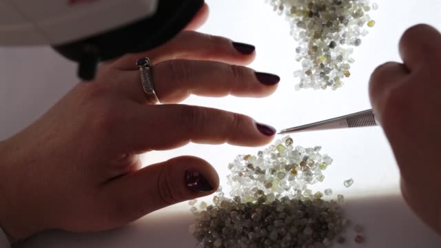 employees use tweezers to sort through a large collection of rough diamonds on sorting tables at the yakutsk diamond trading enterprise , operated by... - rough点の映像素材/bロール